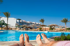 Man and woman sunbathing by the pool at the hotel.  Royalty Free Stock Photos