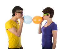 Man and woman with sunglasses blowing balloons Royalty Free Stock Photography