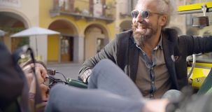 Man and woman with sunglasses smiling,relaxing and talking seated liying on stopped vehicle.Side.Caucasian couple in. Love roadtrip vacation italian travel on stock video footage