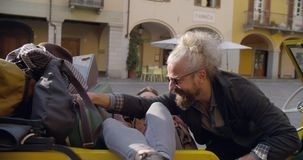 Man and woman with sunglasses smiling,relaxing and talking seated liying on stopped vehicle.Side.Caucasian couple in. Love roadtrip vacation italian travel on stock footage