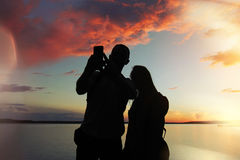 Man and  woman at sunset makes a photo. A man and a woman at sunset makes a photo selfie at the lake Stock Photography