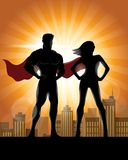Superhero Couple Silhouette with City Skyline Background. Man and woman superhero silhouette Stock Photos