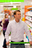 Man and woman in supermarket with shopping cart Royalty Free Stock Photos