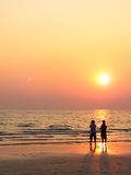 Man and woman sweet lover on the beach with sunset Stock Image