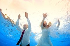 Man and woman swim underwater in the pool with a backdrop of sunlight. Man and women in wedding dresses swim underwater in the pool with a backdrop of sunlight Stock Images
