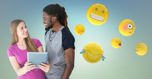 Man and woman with tablet and emojis against blue green background. Digital composite of Man and women with tablet and emojis against blue green background Stock Photography