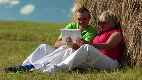 Man and woman with Tablet-PC sits near a haystack stock footage