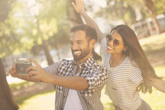Man and woman taking a self portrait. Man and women taking a self portrait outdoors Royalty Free Stock Photos