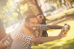 Man and woman taking a self portrait. Man and women taking a self portrait outdoors Royalty Free Stock Photo