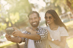Man and woman taking a self portrait. Man and women taking a self portrait outdoors Royalty Free Stock Image