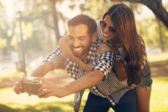 Man and woman taking a self portrait. Man and women taking a self portrait outdoors Stock Images