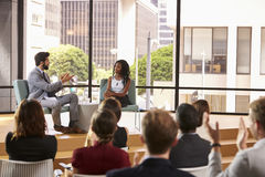 Man and woman talk in front of audience at business seminar stock photos