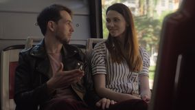Man and woman talking in the bus. Young man and woman friends having a talk during the bus ride in the city stock footage