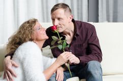Man and woman talking on couch - he is smelling a rose Stock Image