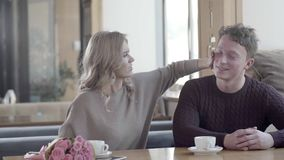 Man and woman talking in cute cafes and laugh. Loving couple. On a date. First Date: woman with beautiful styling and a young man. A bouquet of flowers and two stock footage