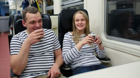 Man and woman talking and drinking tea or coffee. Young man and woman talking and drinking tea or coffee while traveling by train in the evening stock video footage