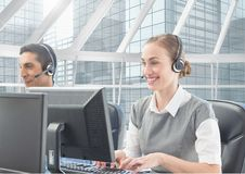Man and woman talking on headset in customer service office. Man and women using computer and talking on headset in customer service office stock image