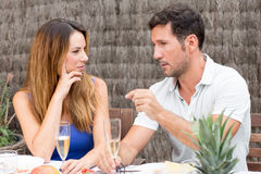 Man and woman talking over a glass of champagne. Happy couple drinking champagne in garden, while boyfriend is explaining some things to his girlfriend Stock Images