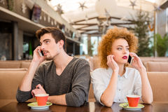 Man and woman talking on the phones in restaurant stock photography