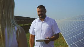 Man and woman talking at solar power plant. Girl interviewing a man at solar electricity station. Generation of clean renewable solar energy. Alternative stock video