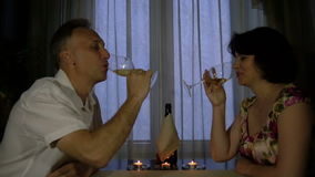 Man and woman talking at the table. Man and woman drinking champagne by candlelight stock video footage