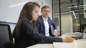 Man and woman talking while taking notes in modern office. Young colleagues sit at table and speak actively, female writes on white sheet with pen. Experienced stock video