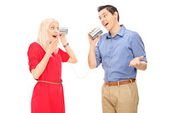 Man and woman talking through a tin can phone Stock Photos