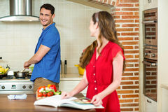 Man and woman talking together while working in kitchen Royalty Free Stock Image