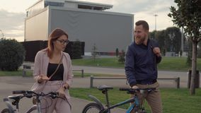 Man and woman talking on a walk rolling bicycles. stock video