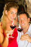 Man and woman tasking wine in cellar. Couple - man and woman- tasting red wine in a cellar, in the background barrels can be seen Royalty Free Stock Photos