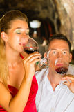 Man and woman tasking wine in cellar. Couple - man and woman- tasting red wine in a cellar, in the background barrels can be seen Stock Photos