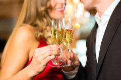 Man and woman tasting Champagne in restaurant. Couple, men and woman, drinking champagne in a fine dining restaurant, each with glass of sparkling wine in hand Royalty Free Stock Image