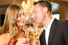 Man and woman tasting Champagne in restaurant Royalty Free Stock Photography