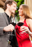 Man and woman tasting wine in restaurant. Couple, men and women, at wine tasting in a restaurant, each with glass of red wine in hand Stock Photography