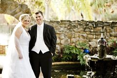 Man and Woman in Their Wedding Outfit With Brown Wall in the Background Near Fountain and Pond during Daytime Stock Image