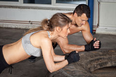 Man and woman on a tire crossfit fitness training Royalty Free Stock Images