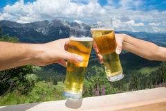 Man and woman toast with beer. With alps mountains in background royalty free stock images