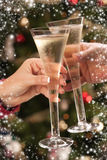 Man and Woman Toasting Champagne in Front of Lights Royalty Free Stock Images
