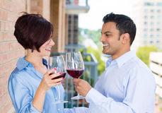 Man and woman toasting wine on outside balcony Stock Image