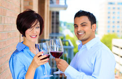 Man and woman toasting wine on outside balcony Stock Photo