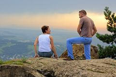 Man and woman on the top of the mountain at sunset Royalty Free Stock Photography
