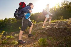 A man and woman tourist with backpack on route of a hike in the. A men and women tourist with backpack on route of a hike in the mountains. Travel, vacation Stock Photography