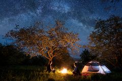 Man and woman tourists sitting at a campfire near tent under trees and beautiful night sky full of stars and milky way Stock Image