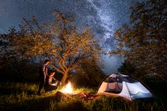 Man and woman tourists standing at a campfire near tent under trees and beautiful night sky full of stars and milky way Royalty Free Stock Images