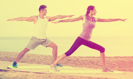 Man and woman training on beach by sea Stock Image