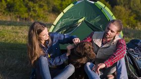 Man and woman traveling with dog at camp. Sitting near camping tent and playing with pet on nature stock video