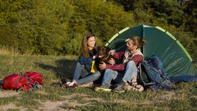 Man and woman traveling with dog at camp. Sitting near camping tent and playing with pet on nature stock video footage