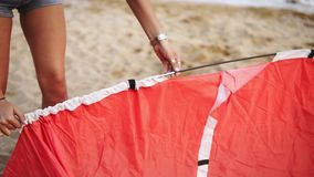 A man and a woman are traveling. Together they set up a red tent on the beach near the sea in windy weather. Close up. Footage stock footage