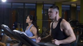 Man and woman jogging at gym. Man and woman on a treadmill at gym stock video footage
