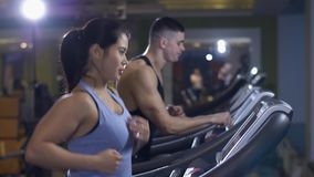 Man and woman on a treadmill. At gym stock video footage